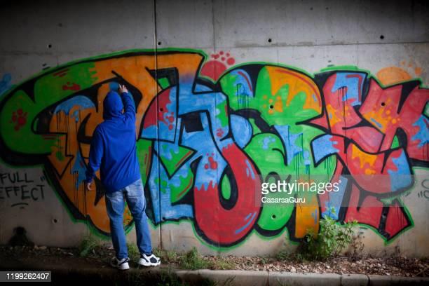 壁に落書きを仕上げたグラフィティアーティスト - ストック写真 - 公共物破壊 ストックフォトと画像