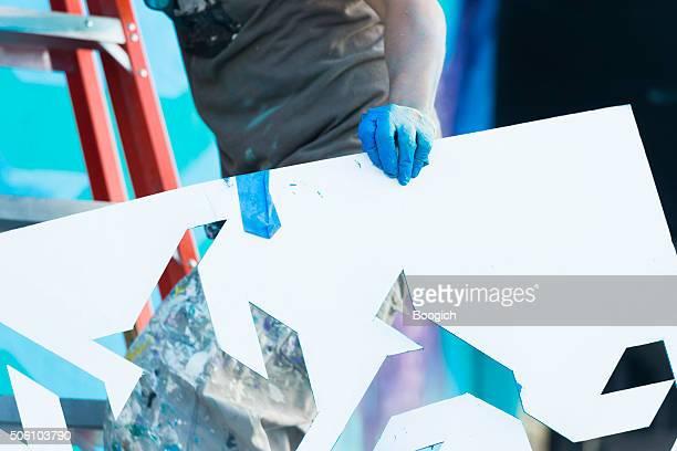Graffiti artista tiene plantilla en escalera de crear obras de arte en Wynwood