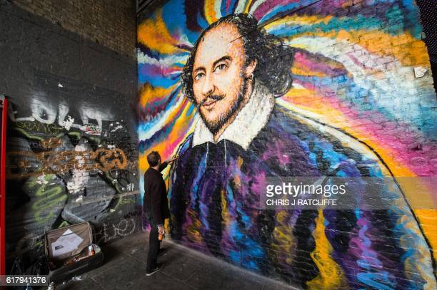 Graffiti artist James Cochran aka Jimmy C works on his mural of William Shakespeare on Clink Street near the Shakespeare's Globe theatre in London on...