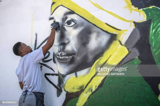 A graffiti artist paints a portrait of the late South African antiapartheid campaigner Winnie MadikizelaMandela exwife of former South African...