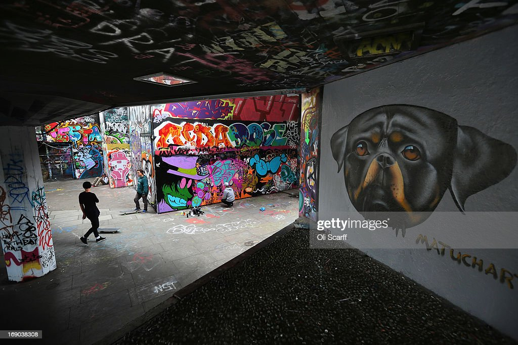 A graffiti artist paints as young men skateboard in the skate park at the Southbank Centre on May 18, 2013 in London, England. Plans are underway to refurbish the Festival Wing, the Queen Elizabeth Hall, Purcell Room and Hayward Gallery complex, including the 'Undercroft', which would be replaced with new arts venues and retail outlets. The skate park, hailed as the birthplace of British skateboarding, is to be moved to nearby Hungerford Bridge, which has caused anger amongst the skateboarding and bmxing community.