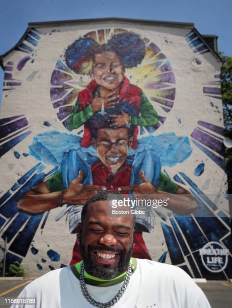 """Graffiti artist Rob Gibbs poses for a portrait with his new mural """"Breathe Life 3,"""" in the Roxbury neighborhood of Boston on June 28, 2019."""
