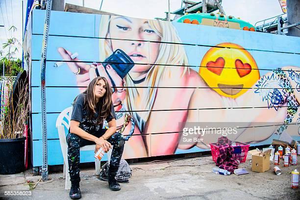 Graffiti artist sitting by painted wall, Venice Beach, California, USA