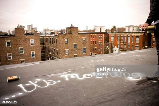 Graffiti artist spray painting on urban rooftop