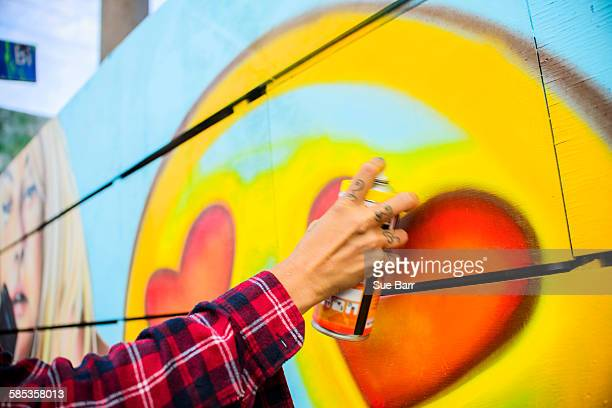 Graffiti artist spray painting wall, Venice Beach, California, USA