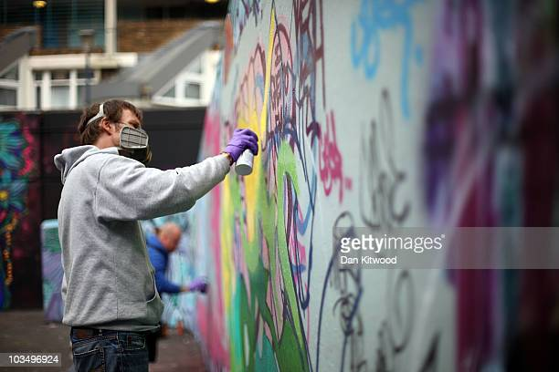 A graffiti artist sprays paint on the walls of an old playground in the Stockwell Park estate on August 19 2010 in London England Graffiti artists...