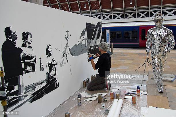 Graffiti artist Tom Cat sprays paint as he creates a dramatic six foot high live art installation alongside the Mirror Man at Paddington Central to...