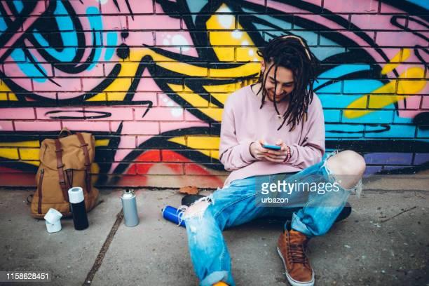 graffiti-künstler mit telefon - eislauf oder rollschuhlauf stock-fotos und bilder