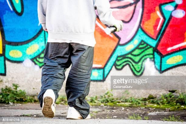 Graffiti Artist Walking Towards Wall with Graffiti