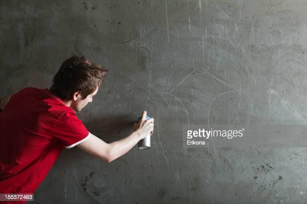 Graffiti artist with blank stone wall