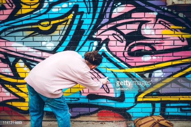 graffiti artist with dreadlocks - street artist stock photos and pictures