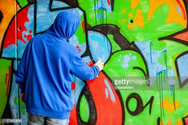 graffitista che scrive a parete - murale foto e immagini stock