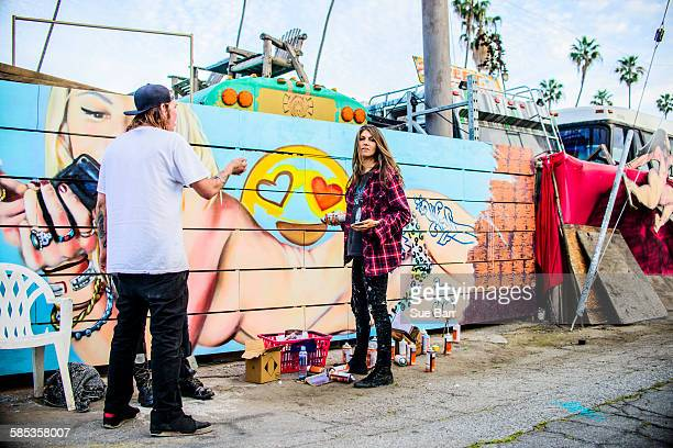 Graffiti artists by painted wall, Venice Beach, California, USA