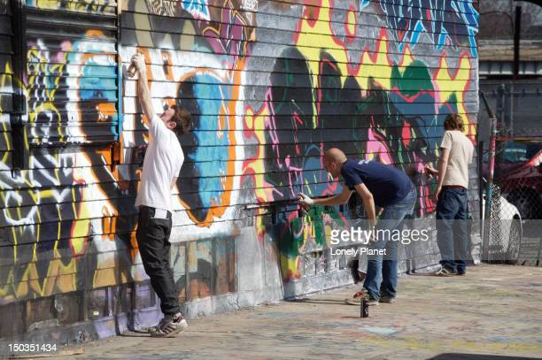 Graffiti artists creating new artwork at Five Pointz.