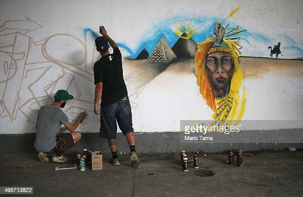 Graffiti artists paint during celebrations marking Day of the Favela in the Madureira favela community on November 4 2015 in Rio de Janeiro Brazil...