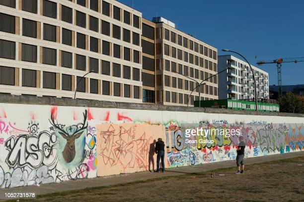 Graffiti artists work on a former section of the Berlin Wall called the East Side Gallery near newlycompleted office and apartment buildings on...