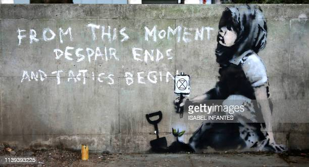 TOPSHOT Graffiti artwork suspected to have been created by the British street artist Banksy is pictured opposite the environmental protest group...