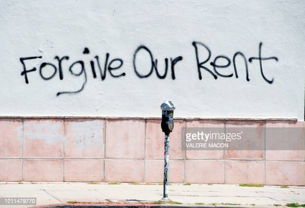 Graffiti asking for rent forgiveness is seen on a wall on La Brea Ave on National May Day amid the Covid-19 pandemic, May 1 in Los Angeles,...