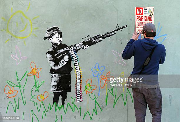 A graffiti attributed to secretive British artist Banksy depicting a child wielding a machine gun in black and white surrounded by colored flowers is...