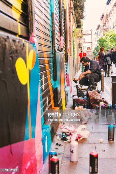 Graffiti boy spray painting in the street