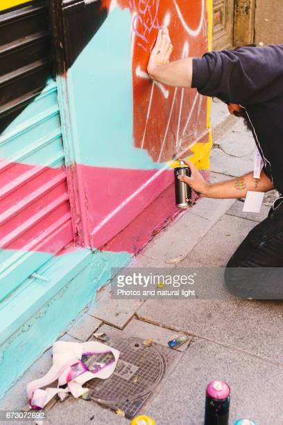 Graffiti boy, spray painting in the street