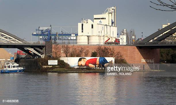 A graffiti by artists Justus Becker and Oguz Sen depicts the drowned Syrian refugee boy Alan Kurdi at the harbor in Frankfurt am Main Germany on...