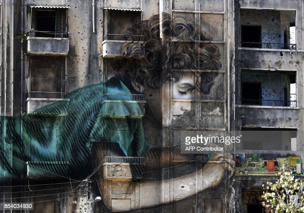 A graffiti by CubanAmerican artist Jorge RodriguezGerada of a boy working on an electronic device is seen on a building riddled with holes from...