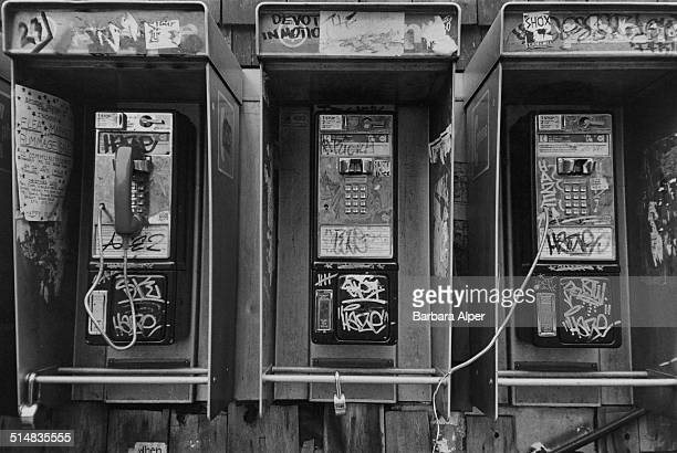 Graffiti covered broken pay phones in New York City USA December 1981