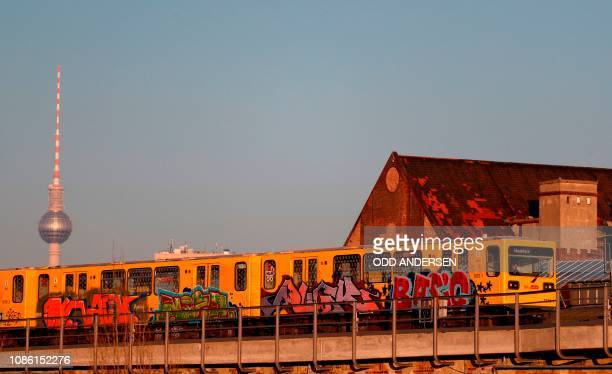 A graffiti covered U2 subway train is seen on the tracks with the Berlin TV tower in the background on January 22 2019 in Berlin