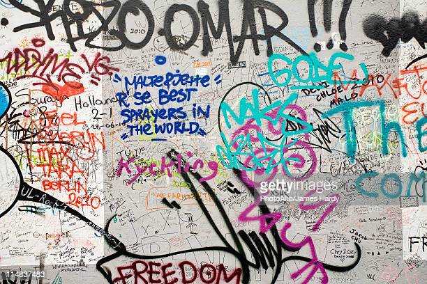 graffiti covering a section of the berlin wall, berlin, germany - graffiti foto e immagini stock