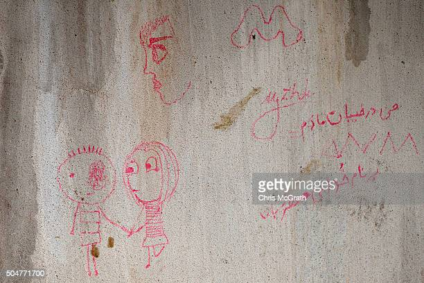Graffiti drawn on a wall in a room at an unfinished resort complex used by refugees and migrants while waiting for smugglers boats to take them to...