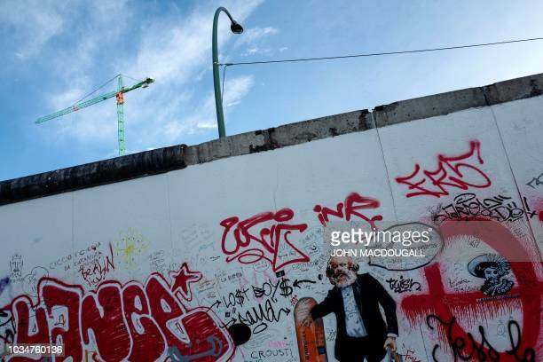 A graffiti featuring a likeness of Karl Marx appears on the socalled East Side Gallery a 13 kmlong stretch of the Berlin wall in Berlin on September...