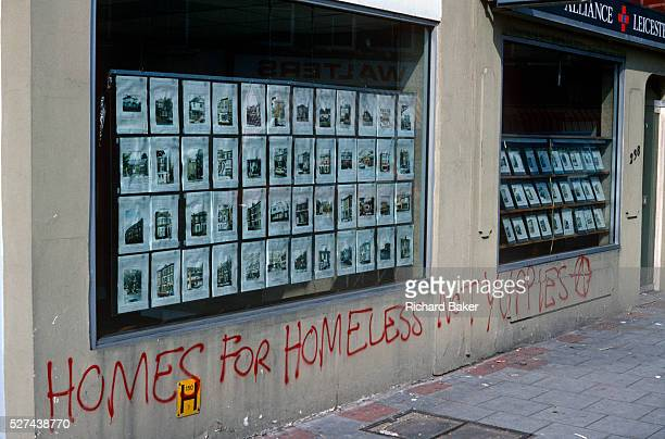 Graffiti has been sprayed in red with aerosol on the wall of an estate agent in Herne Hill South London England 'Homes for the Homeless not Yuppies'...