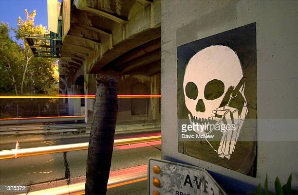 Graffiti image of a skull holding a cell phone is painted on an underpass along the Pasadena Freeway, July 11, 2001 in Los Angeles, CA. California...