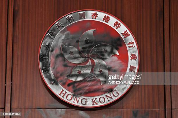 Graffiti is seen on the bauhinia flower emblem of Hong Kong behind the speakers chair in the main chamber of the Legislative Council during a media...
