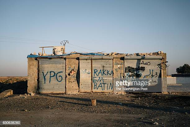 Graffiti made by members of the YPG shortly after capturing Tal Samin from Islamic State militants reads 'Raqqa we are coming'