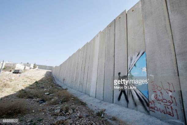 Graffiti made by the graffiti artist Banksy is seen on Israel's highly controversial West Bank barrier in Abu Dis on August 6, 2005. Banksy has made...