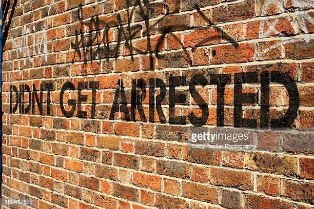 Graffiti message stencilled on a brick wall