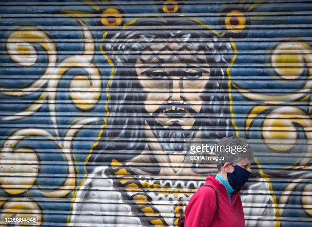 Graffiti of a closed shop depicting a image of Christ, is seen as a woman wearing a face mask walking past during a Holy Monday in downtown Malaga....