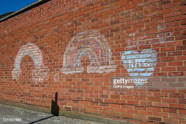 Graffiti of rainbows 'Stay at home' and a NHS within a heart shape are seen on a wall as coronavirus lockdown continues Rainbows are used as a symbol...