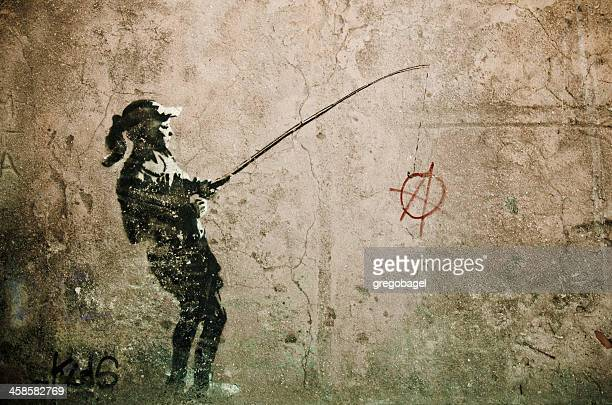 Graffiti of young girl fishing for anarchy sign