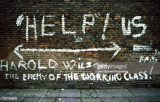 Graffiti on a brick wall in Bolton Greater Manchester 1976 It reads 'Help Us Harold Wilson the enemy of the working class'