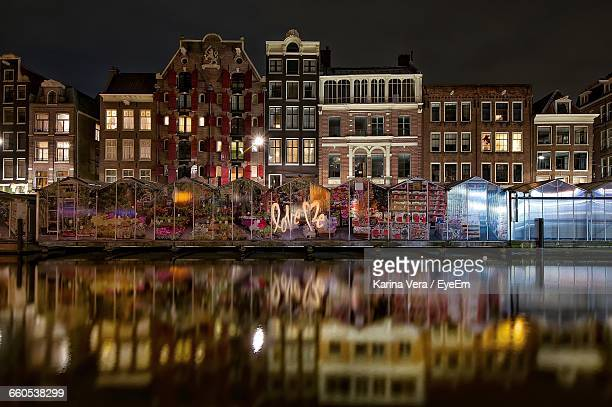Graffiti On Buildings By Canal At Night
