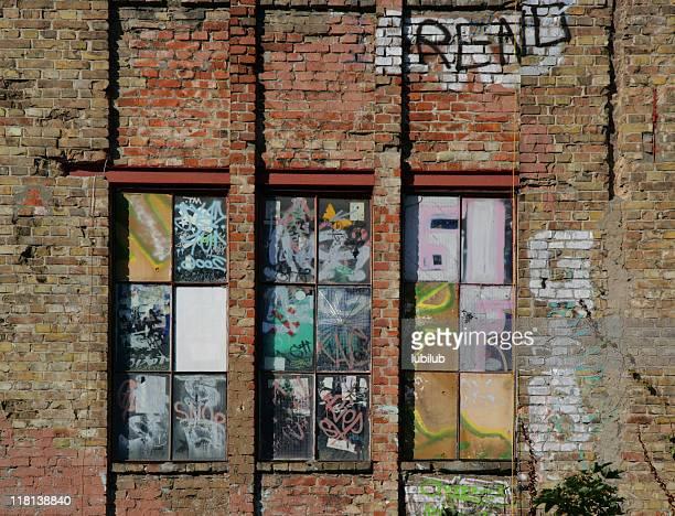 Graffiti de la pared de ladrillo viejo y ventanas en Berlín, Alemania