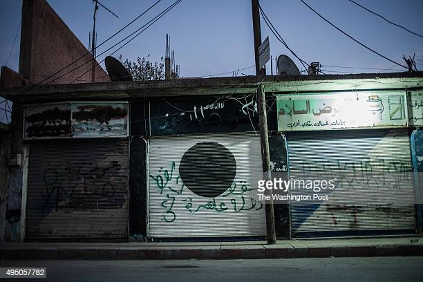 Graffiti on the door of a shuttered store formerly selling ISISapproved products reads 'ISIS fell the whore state fell' Next door graffiti reads...