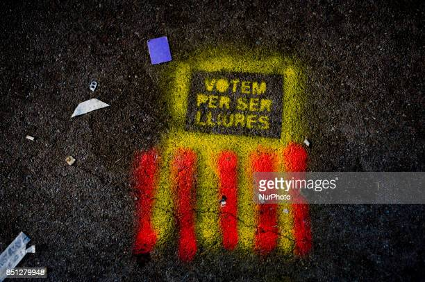 A graffiti on the floor reading 'we vote to be free' and the colors of the catalan flag is seen in front of the Catalan High Court building in...