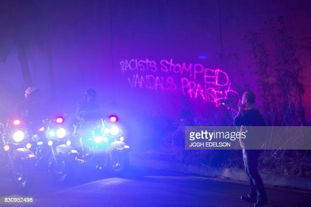 Graffiti on the wall is reflected in the police lights as protesters march down an onramp after blocking Interstate 580 to rally against racism in...