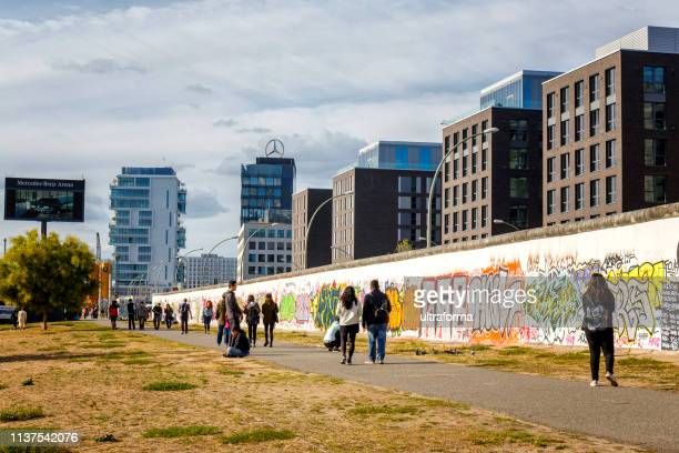 graffiti paintings on the east side gallery wall of berlin germany - east stock photos and pictures