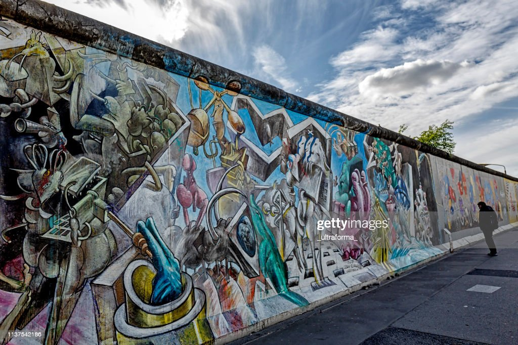 Graffiti paintings on the East Side Gallery wall of Berlin Germany : Stock Photo