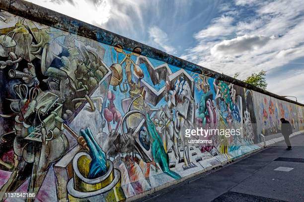 graffiti paintings on the east side gallery wall of berlin germany - east stock pictures, royalty-free photos & images